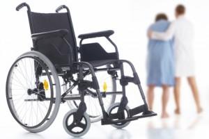 Krankenschwester führt einen Patienten von seinem Rollstuhl weg